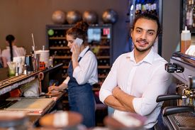 Happy young cross-armed waiter in white shirt standing in front of camera on background of colleague talking to client on the phone