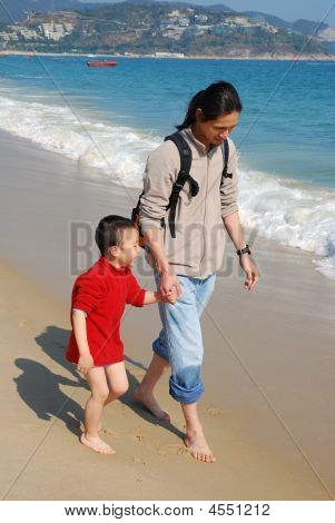 Father and son walking in the surfy beach poster