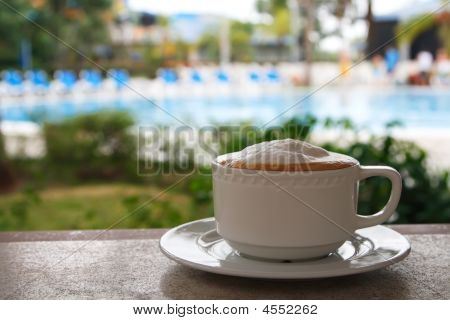 Coffee Latte Macchiato In White Mug Against Swimpool Background