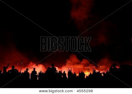 A crowd of people in front of a firy explosive background. poster