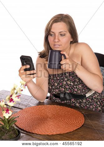 Woman Sitting At Table On Cell Phone