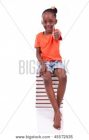Cute Black African American Little Girl Seated In A Stack Of Books Making Thumbs Up - African People