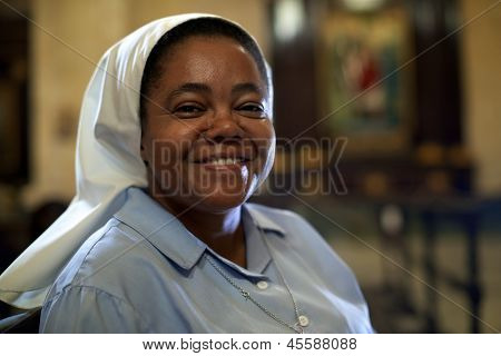 Woman and religion portrait of catholic nun praying in church and looking at camera poster