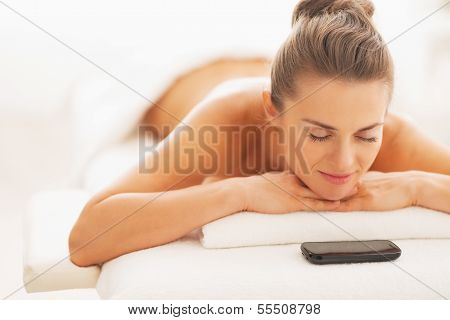 Relaxed Young Woman And Cell Phone Laying On Massage Table