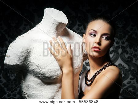 Attractive young lady with the statue over the retro background