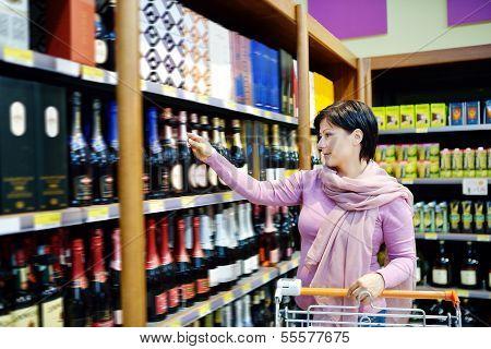 Woman Shopping And Choosing Liquor At Supermarket