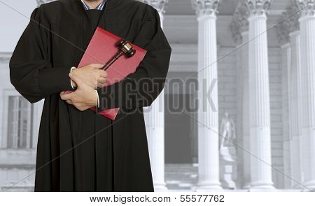 The judge hammer with a judge on the background of the courthouse