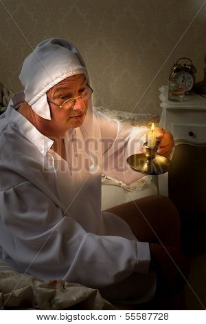 Funny vintage man going to bed with a candlestick