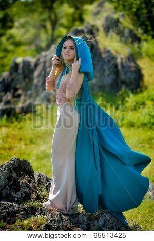 beautiful woman with blue cloak posing  outdoor