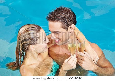 Happy couple in swimming pool toasting with glass of champagne