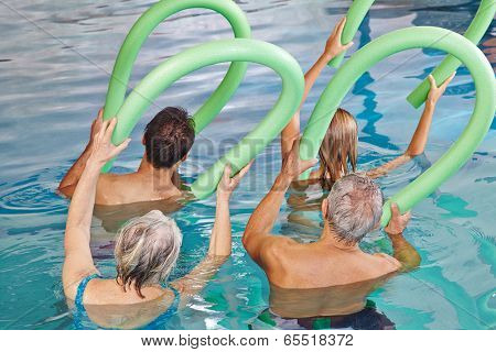Group of senior people doing aqua fitness from behind with swim noodles