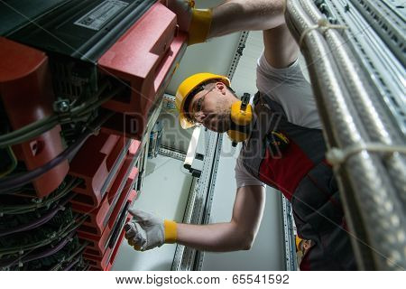 Electrician in a safety hat and headphones on a factory