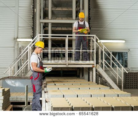 Worker and foreman in a safety hats on a factory