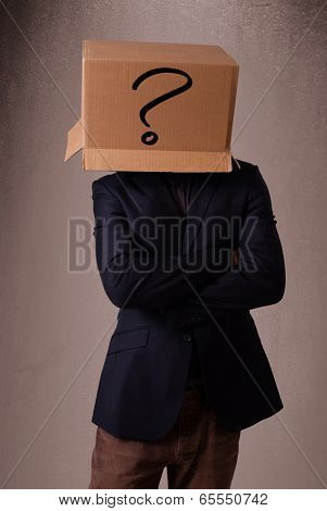 Young man standing and gesturing with a cardboard box on his head with question mark poster