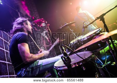 Drummer (blurred motion) playing on drum set on stage. Focus on the drum and microphone.