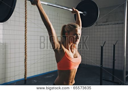 Strong woman lifting barbell as a part of exercise routine. Fit young woman lifting heavy weights at gym. ** Note: Shallow depth of field ** Note: Visible grain at 100%, best at smaller sizes poster