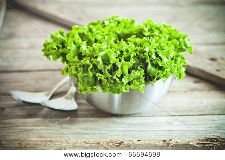 lettuce salad in metal bowl and spoons closeup on rustic wooden board
