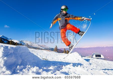 Snowboarder holding board during jump