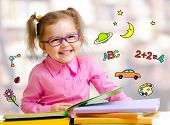 Happy child girl in glasses reading books in library poster