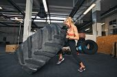 Muscular young woman flipping tire at gym. Fit female athlete performing a tire flip at gym. ** Note: Shallow depth of field ** Note: Visible grain at 100%, best at smaller sizes poster