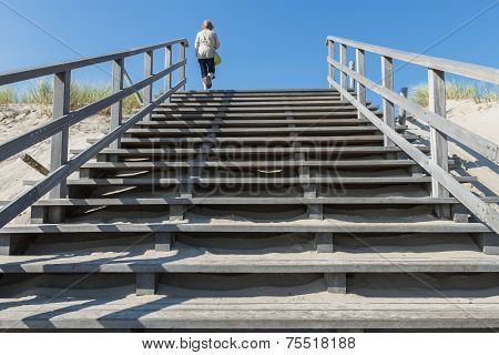 Tourist On Stairs Of Beach Entrance