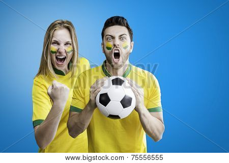 Brazilian couple celebrate on blue background with her face painted