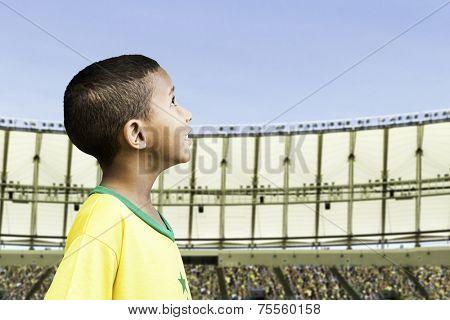 Brazilian little boy looks to the sky on the stadium