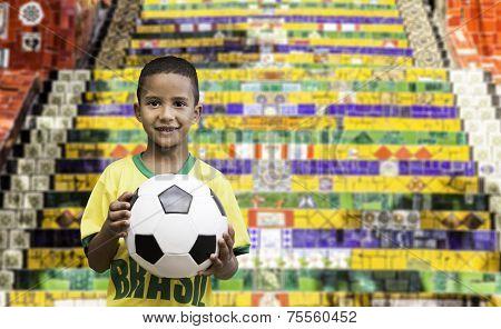 Brazilian little boy holds a soccer ball in Rio de Janeiro, Brazil