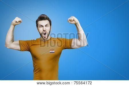 Dutchman soccer player celebrates on blue background