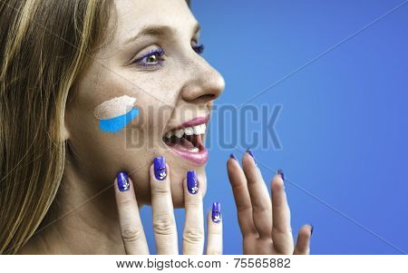 Blonde Argentinian fan celebrates on blue background