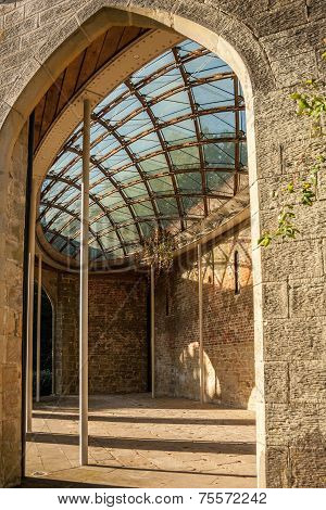 The interior of a stone brick building with a patterned glass ceiling. poster