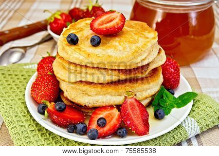 Flapjacks with strawberries and blueberries on napkin