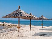 beach bar parasols on the empty beach poster