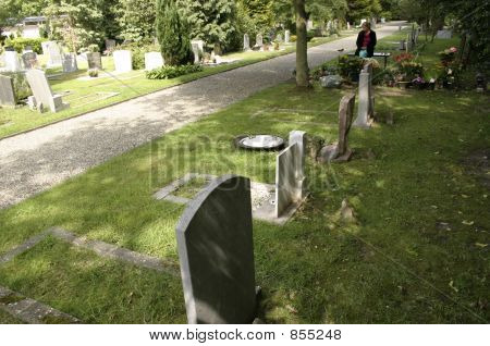 woman mourning over grave in cemetery