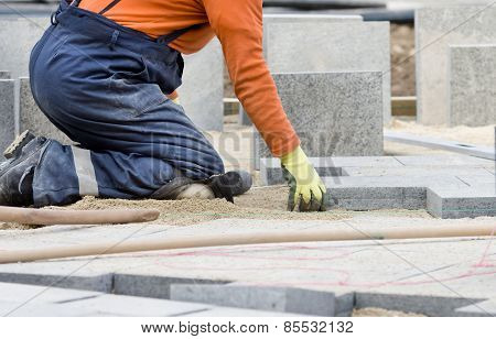 Construction worker on knees placing stone tiles in sand for pavement poster