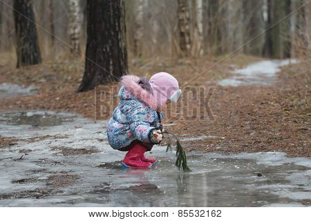 Two years old girl sitting in icy puddle