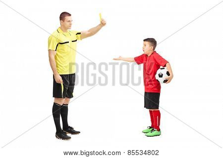 Football referee showing yellow card to a junior soccer player isolated on white background