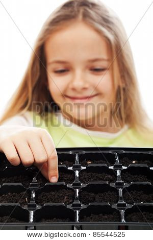 Little girl planting putting seeds into germination tray - growing food concept