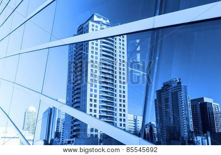 Buildings Reflected In Windows Of Office Building