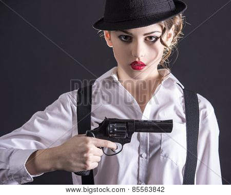 Beautiful and dangerous. Young female gangster holding the gun. isolated on dark background. poster