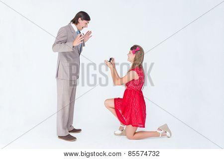 Pretty hipster on bended knee doing a marriage proposal to her boyfriend on white background