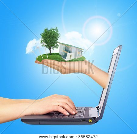 White house in hand with green roof of screen laptop. Background sun shines brightly on right