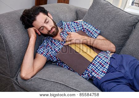 man sleeping on sofa couch while reading book at home living room lounge