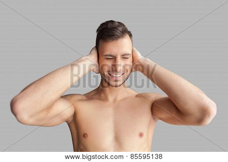 Can't Hear It Anymore. Handsome Young Muscular Man Covering His Ears With Hands And Keeping Eyes Clo