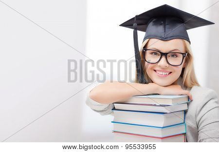 education concept - picture of happy student in graduation cap with stack of books