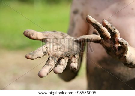 Close Up On Muddy Hands Of Little Boy