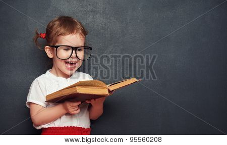 Funny Happy  Girl Schoolgirl With Book From Blackboard
