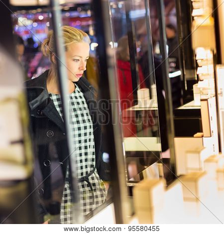 Beautiful blonde lady standing in front of showcase in beauty store, admiring new perfume collection. poster