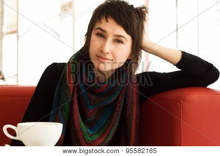 Portrait Of A Young Beautiful Girl In A Knitted Striped Scarf And A Cup Of Tea
