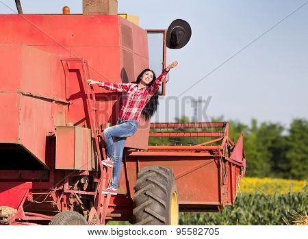 Happy young woman climbing on combine harvester and throwing her hat in the air poster